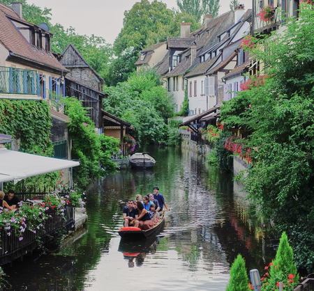 Colmar, France - Aug 2015: Tourist in little boat cruise the canals in medieval Colmar, in Alsace.