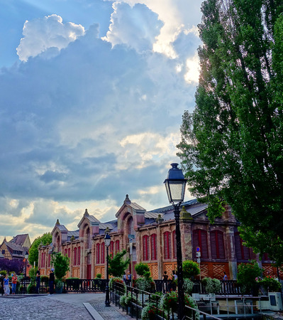 Colmar, Alsace, France - Aug 2015: Atmospheric skies hang over the historic building that houses the Colmar Farmers Market Editorial