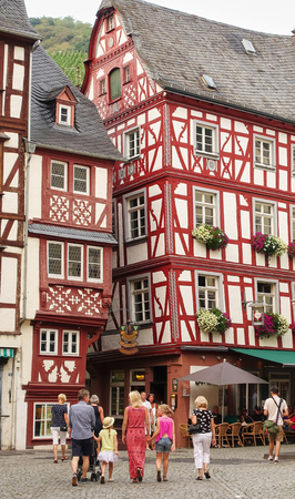 Bacharach, Germany - Aug 2015: Family on summer holidaywalks the cobblestone streets with medieval buildings