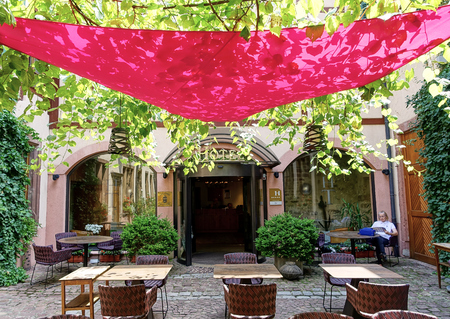 Colmar, France - Aug 2015: Triangular Red Canopy provides shade in this hotel courtyard eating area