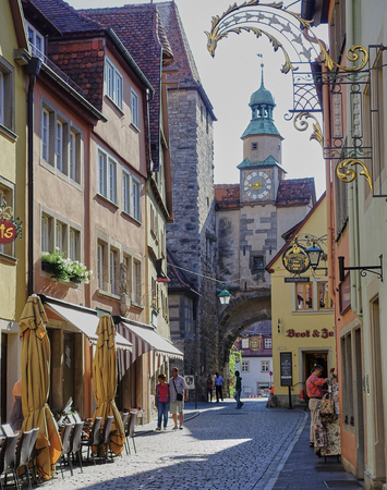Rothenburg, Germany - Aug 2015: Medieval street scene with gate tower and narrow arch way through walled fortification along with a few tourist enjoying the Romantic Road