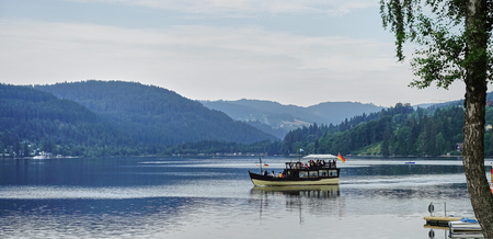 Lake Titisee, Black Forest, Germany - Aug 2015: Boat takes tourists on a cruise of this spa resort town lake in earl evening