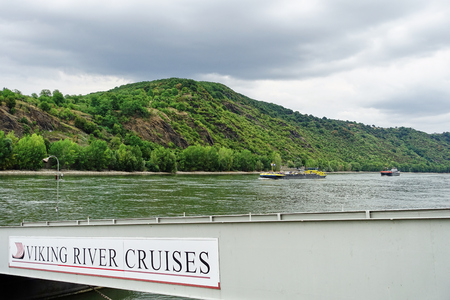 Rhine River landscape with barges in the water, and a Viking River Cruises sign on a gangway at the river bank. Boppard, Germany - Aug 2015