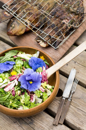 utencils: flower salad and grilled fish with utencils on wooden table Stock Photo