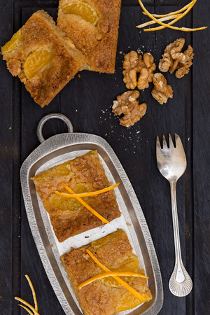 blondie: brown cake slices with mandarin and walnuts. Vertical image.