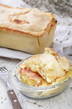 potatoe: potatoe pie with bacon on white wooden table. Vertical image.