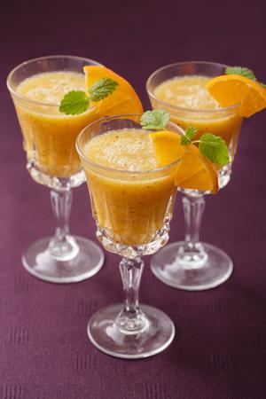cool background: three stemwares with orange smoothie inside