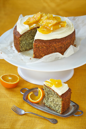 homemade cake: a sponge cake with poppy seeds, oranges and cream on a golden background