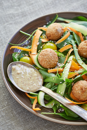 shoestring: meatballs with shoestring vegetables and a spoon of  porridge