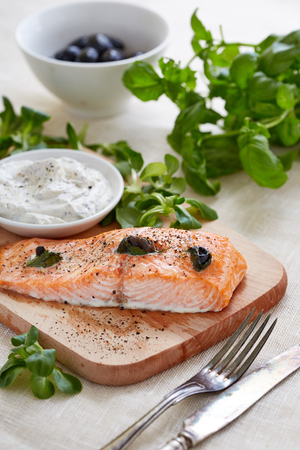 fish sauce: food still life photography of salmon fillet, Tartar sauce on a cutting board and basil leaves