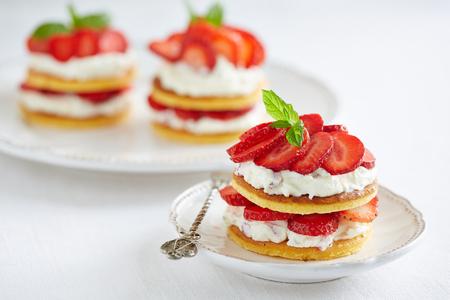 Drie porties van pannenkoeken met slagroom en aardbeien Stockfoto - 50141506