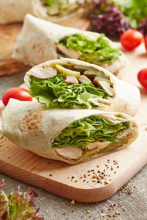 doner: wrap with chicken and lettuce on the wooden cutting board