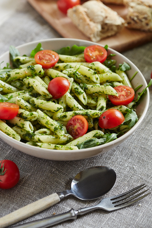 rocked: macaroni with chopped parsley halved cherry tomatoes and rocket salad on a sackcloth Stock Photo