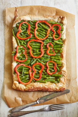 green bean: a top view of green bean and paprika tart on the piece of parchment
