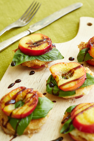 baked nectarine rounds decorated with basil and chocolate on the wooden cutting board