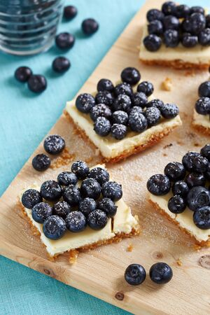 glass topped: square pieces of blueberry cheesecake on the cuttingboard Stock Photo
