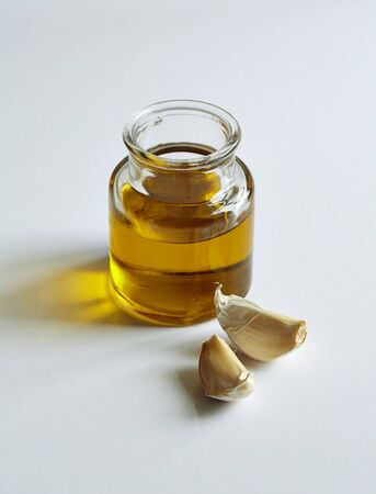 garlic cloves: a jar of oil and two garlic cloves in the white background