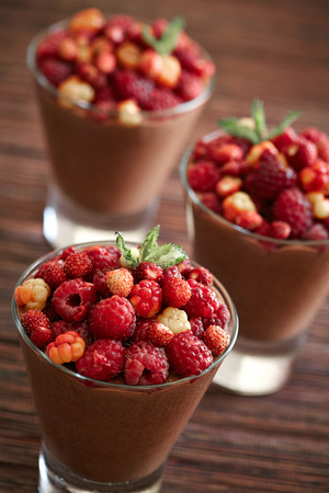 portions: three portions of chocolate mousse with berries on the top