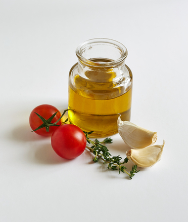 garlic cloves: a jar of oil, two garlic cloves, tomatoes and a savory twig in the white background