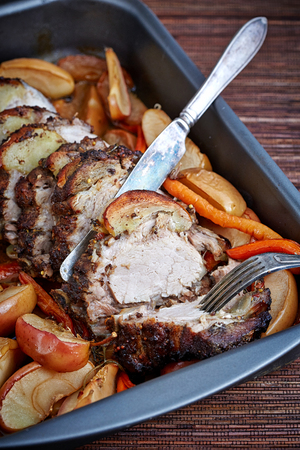 roasting pan: meat roll with baked fruit and vegetables in the roasting pan on the bamboo mat