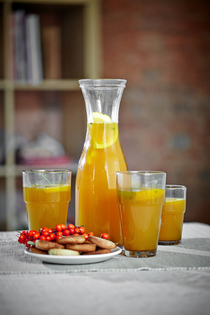 ascorbic acid: buckthorn drink with lemon slices and cookies on the table