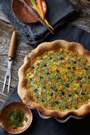 recipe decorated: appetizing home-made vegetable tart in the dark background