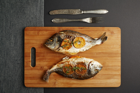 stuffed fish: a top view of a pair of baked filled of oranges doradas on the wooden cutting board in the grey background