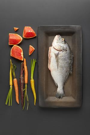 dorada: a vertical top view of raw dorada , carrots and grapefruit in the dark background Stock Photo