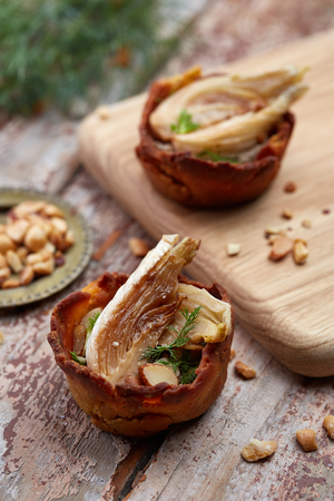 two home-made tartelettes stuffed with mushrooms and peanuts on the wooden table