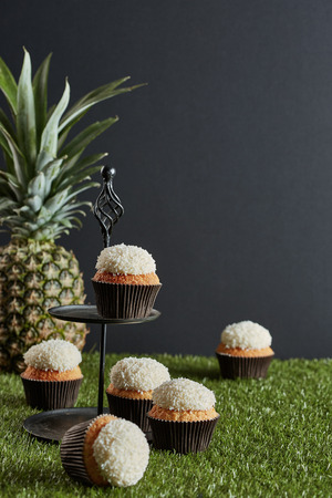 six small cakes on the tier tray and artificial pitch and a pineapple in the dark grey background Stock Photo
