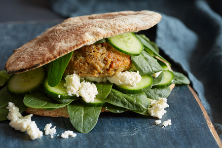 a horizontal image of pita bread sandwich with a cutlet, cucumber slices , basil and farm cheese