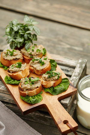 roasted open-face sandwiches with baba ghanoush topping served on the wooden cutting board isolated on the vintage wooden background Stock Photo