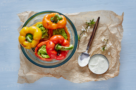 meatless: uncooked vegan stuffed bell peppers in a glass pot and bechamel sauce on parchment
