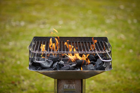 a brazier with charcoal and flame in it on the grass