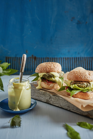 two appetizing hamburgers on the wooden plank and a jar with sauce in the blue background