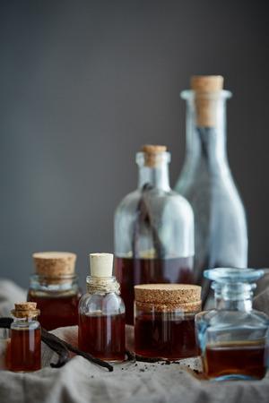verticale foto van een groep flessen met huisgemaakt vanilleuittreksel op donkergrijze achtergrond
