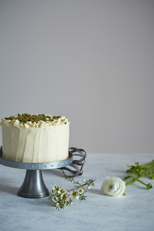 a cake on the cakestand decorated with nuts and ground rosemary and custard on the table