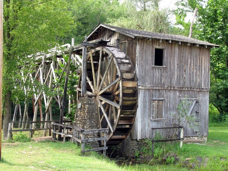 Old water wheel with a bridge over a river photo