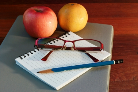 Back to school concept  An apple, pencils and glasses on books photo