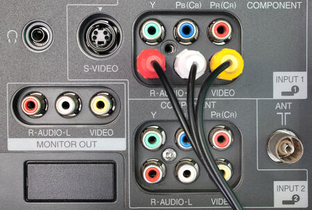 plugged in': Wires plugged in to the connection panel of tv player Stock Photo