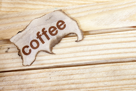 burnt paper: burnt paper and  coffee text on wood background