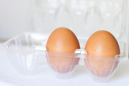 egg box: plastic egg box with brown eggs