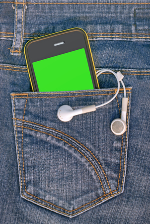 handsfree device: A mobile phone in the pocket of denim trousers.