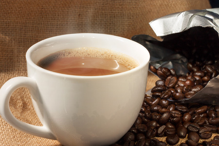 sacco juta: tazza di caffè e chicchi di caffè close-up su sfondo sacco di juta