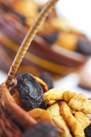 Dried fruits and nuts in bowl and basket on table Stock Photo - 20390611