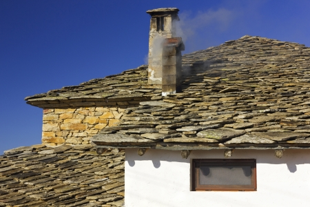Old house with a smoky chimney Stock Photo