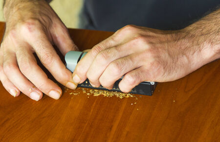 self dependent: Man rolling cigarettes using fresh tobacco Stock Photo