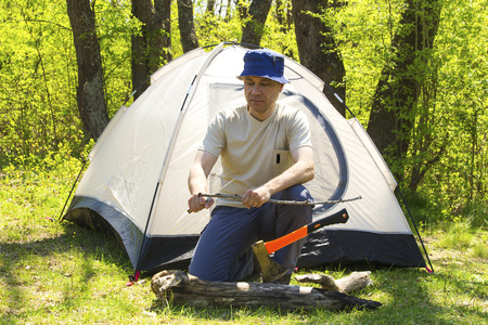 ax man: Man with an ax chopping wood to tent Stock Photo