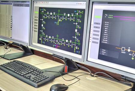 Computadoras y monitores con diagrama esquemático para supervisión, control y adquisición de datos en la moderna sala de control eléctrico
