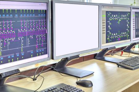 Computadoras y monitores con diagrama esquemático para supervisión, control y adquisición de datos en la moderna sala de control eléctrico Foto de archivo